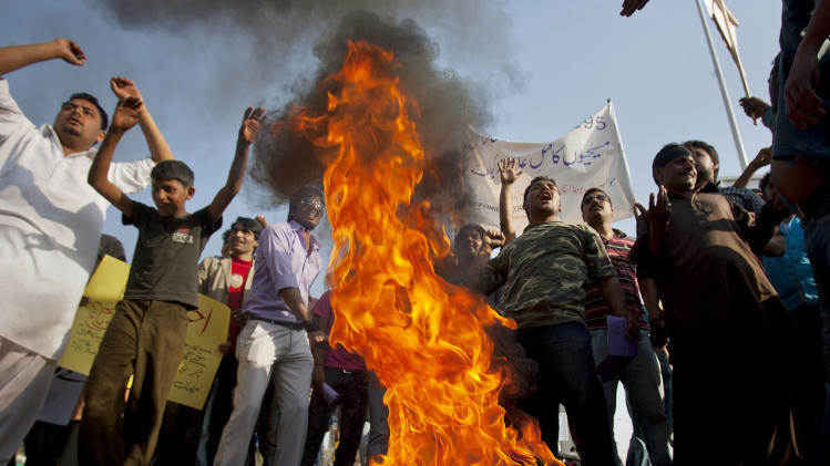 Pakistani Christians chants slogans after they burn a tire during a demonstration demanding that the government rebuild their homes after they were burned down following an alleged blasphemy incident, in Islamabad, Pakistan, Sunday, March 10, 2013. The incident in Lahore began on Friday, March 8, 2013 after a Muslim accused a Christian man of blasphemy, an offence that in Pakistan is punished by life in prison or death. (AP Photo/Anjum Naveed)