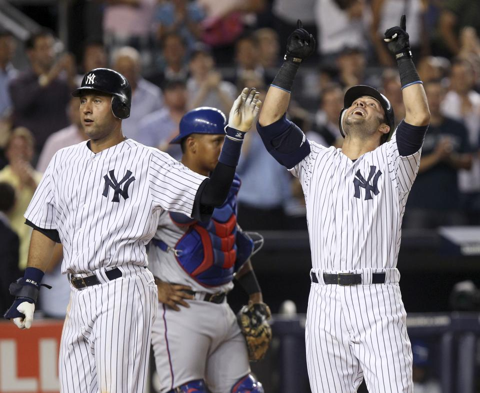 New York Yankees' Nick Swisher, right, celebrates his two-run homer with Derek Jeter during the seventh inning of a baseball game against the Texas Rangers on Tuesday, Aug. 14, 2012, at Yankee Stadium in New York. (AP Photo/Seth Wenig)