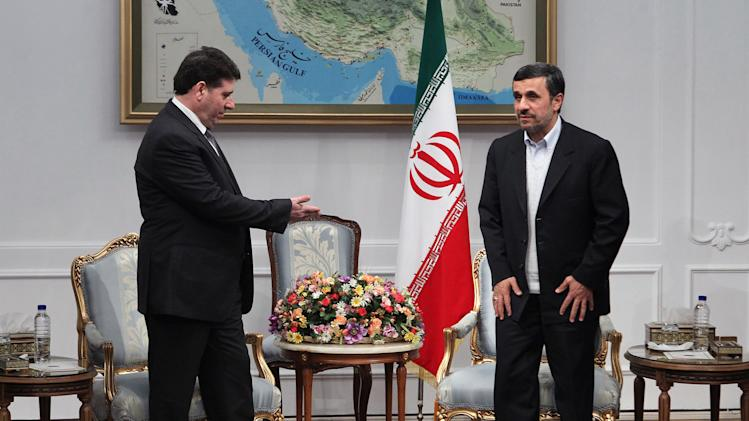 Syrian Prime Minister Wael Nader al-Halqi, left, gestures to Iranian President Mahmoud Ahmadinejad, at the start of their meeting in Tehran, Iran, Tuesday, Jan. 15, 2013. (AP Photo/Fars News Agency/Mehdi Ghasemi)