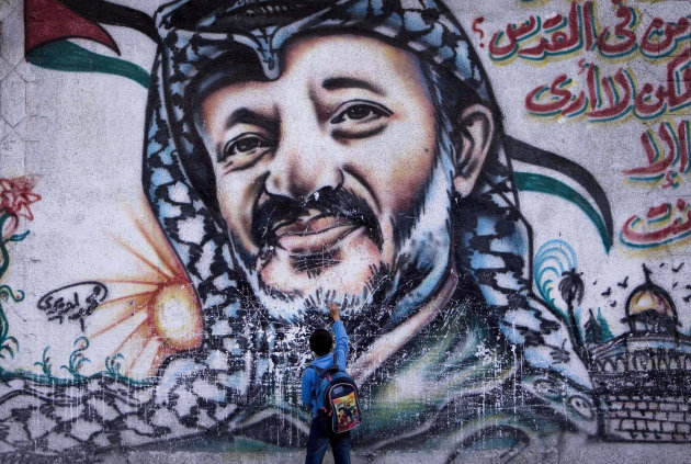 "FILE - In this Nov. 10, 2009 file photograph, a Palestinian boy touches a mural of the late leader Yasser Arafat, in Gaza City. French judges will visit the West Bank town of Ramallah as part of a probe into the death of Yasser Arafat, the widow of the late Palestinian leader said Wednesday, Sept. 5, 2012. Arafat died eight years ago in a French military hospital from a stroke, but the underlying causes of the illness that preceded his death have never been determinedWriting in Arabic reads ""In Jerusalem - who is in Jerusalem - I only see you"". (AP Photo/ Tara Todras-Whitehill, File)"