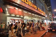 "Fans wait outside for ""The Dark Knight Rises"" midnight premiere on July 19 in New York City. Warner Brothers is withholding data on weekend box office takings from ""The Dark Knight Rises"" out of respect for victims of the Colorado massacre"