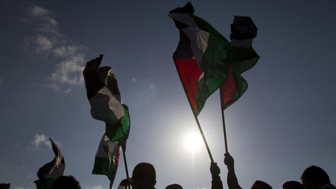 """Arab Israeli protesters wave Palestinians flags as they gather to mark the annual Land Day event in the Arab Village of Dir Hana, northern Israel, Friday, March 30, 2012. About 2,000 Arab-Israeli protesters demonstrated in northern Israel, where a large portion of Israel's Arab minority lives. The """"Land Day"""" rallies are an annual event marked by Israeli Arabs and Palestinians in the West Bank and Gaza who protest what they say are discriminatory Israeli land policies. (AP Photo/Ariel Schalit)"""