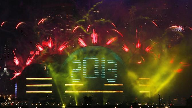 Fireworks explode in front of the Hong Kong Convention and Exhibition Centre over the Victoria Harbor as celebrating the 2013 New Year in Hong Kong Tuesday, Jan. 1, 2013  (AP Photo/Kin Cheung)