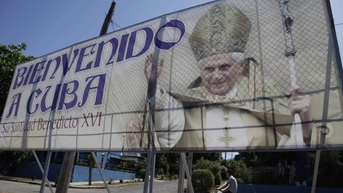 A man rides his bicycle past a billboard welcoming Pope Benedict XVI, just days before his arrival, in Havana, Cuba, Wednesday March 21, 2012. Pope Benedict XVI's trip to Latin America takes him to the region's most Catholic country; Mexico, and then Cuba, where churches are mostly empty and until the 1990s, believers were barred from the Communist Party. (AP Photo/Javier Galeano)