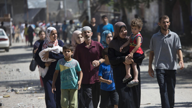 Palestinians return to the heavily bombed Gaza City neighborhood of Shijaiyah, close to the Israeli border, Friday, Aug. 1, 2014. A three-day Gaza cease-fire that began Friday quickly unraveled, with Israel and Hamas accusing each other of violating the truce. (AP Photo/Dusan Vranic)