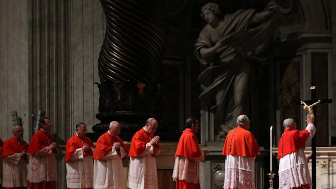 Cardinals line up to touch the Crucifix during the Passion of Christ Mass inside St. Peter's Basilica, at the Vatican, Friday, March 29, 2013. Pope Francis began the Good Friday service at the Vatican with the Passion of Christ Mass and hours later will go to the ancient Colosseum in Rome for the traditional Way of the Cross procession. (AP Photo/Gregorio Borgia)