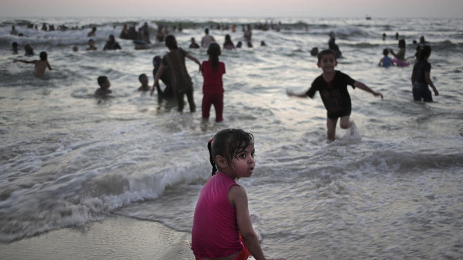 In this June 16, 2015 photo, Palestinians enjoy a summer day on the beach of Gaza City. A year after the most destructive war in Gaza yet, Hamas remains in control, despite signs of mounting frustration and a poll indicating half the residents would emigrate if borders were open. (AP Photo/Khalil Hamra)