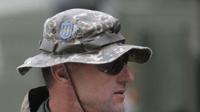A Ukrainian volunteer soldier, wearing a headgear with an emblem of WWII  SS Galician division that had fought against the Soviet Army, waits to be sent to the country's east in a military base in the village of Novi Petrivtsi near Kiev Tuesday, Sept. 30, 2014. Eastern Ukraine has seen its worst violence in more than a week. Officials say fighting between pro-Russian rebels and government troops has killed at least 12 people and wounded 32. Violence has continued despite a cease-fire that was declared more than three weeks ago. (AP Photo/Efrem Lukasky)