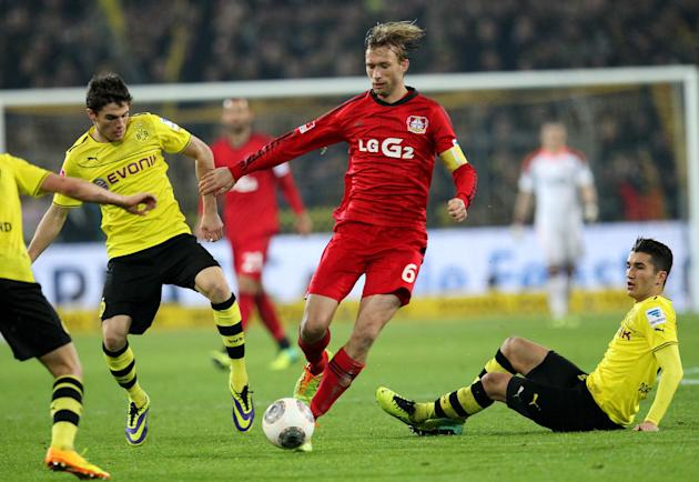 Dortmund's Nuri Sahin, right, and Erik Durm, left challange for the ball with Leverkusen's Simon Rolfes during the German first division Bundesliga soccer match between Borussia Dortmund and B
