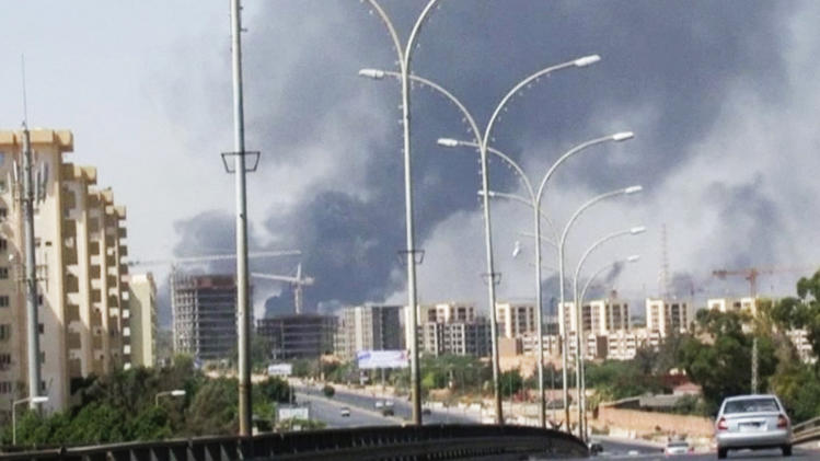 In this image made from video by The Associated Press, smoke rises from the direction of Tripoli airport in Tripoli, Libya, Sunday, July 13, 2014. Rival militias battled Sunday for the control of the international airport in Libya's capital, as gunfire and explosions echoed through the city and airlines canceled some international flights. (AP Photo)