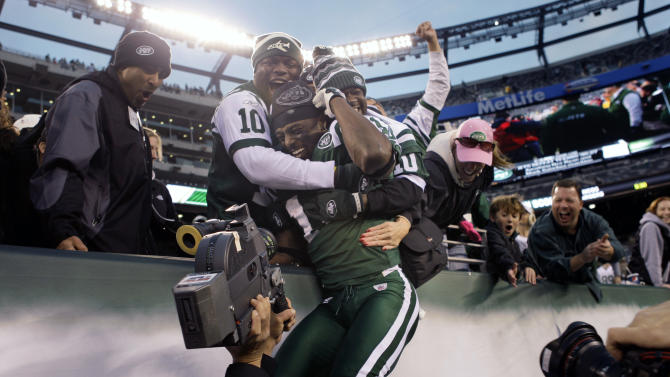 New York Jets' Santonio Holmes jumps into the stands after an NFL football game against the Houston Texans at New Meadowlands Stadium, Sunday, Nov. 21, 2010, in East Rutherford, N.J. The Jets won the game 30-27.  (AP Photo/Seth Wenig)