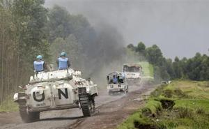U.N. peacekeepers drive tank as they patrol past deserted Kibati village
