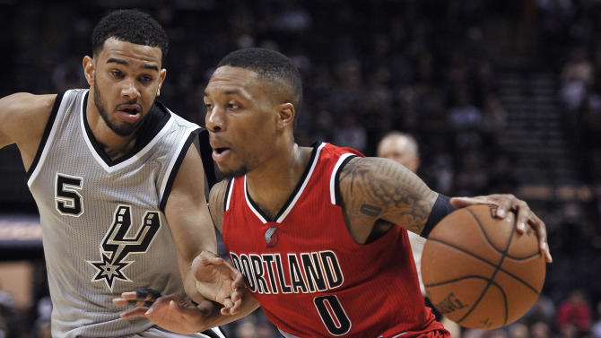 Portland Trail Blazers guard Damian Lillard (0) drives around San Antonio Spurs guard Cory Joseph during the second half of an NBA basketball game, Friday, Dec. 19, 2014, in San Antonio. Portland won 129-119 in triple overtime. (AP Photo/Darren Abate)