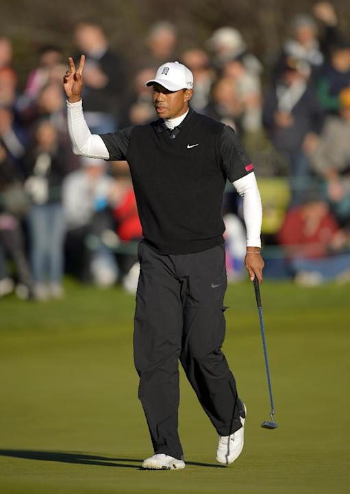 Tiger Woods acknowledges fans after making a birdie putt on the 18th green during the third round of the Northwestern Mutual World Challenge golf tournament at Sherwood Country Club, Saturday, Dec. 7,