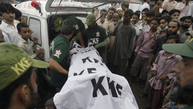 Pakistani rescue workers load a dead body into an ambulance after recovering from a burnt garment factory in Karachi, Pakistan on Wednesday, Sept. 12, 2012. Pakistani officials said the death toll from devastating factory fires that broke out in two major cities has risen to 128. Hospital official Tariq Kaleem says the fire at a garment factory in the southern Pakistani city of Karachi killed 103 people. A blaze at a shoe factory in the eastern city of Lahore killed 25 people. (AP Photo/Fareed Khan)