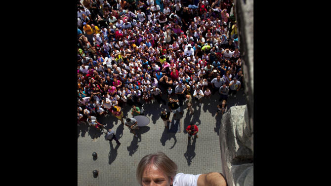 Tourists and residents watch French daredevil Alain Robert scales up a school building without using ropes or a safety net in Old Havana, Cuba, Tuesday, Feb. 5, 2013. The 50-year-old Robert took 15 minutes to ascend the three stories of the graceful stone building, which offered little in the way of hand- and footholds. Robert has scaled the planet's loftiest skyscrapers from the Empire State Building to Dubai's Burj Khalifa, the world's tallest.  (AP Photo/Ramon Espinosa)