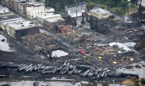 Workers comb through the debris after a train derailed causing explosions of railway cars carrying crude oil Tuesday, July 9, 2013 in Lac-Megantic, Que. THE CANADIAN PRESS/Paul Chiasson