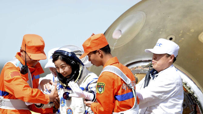 In this photo released by China's Xinhua News Agency, Chinese astronaut Wang Yaping, center, goes out of the re-entry capsule of China's Shenzhou 10 spacecraft after its successful landing at the main landing site in Siziwang Banner, north China's Inner Mongolia Autonomous Region on Wednesday, June 26, 2013. The space capsule with three astronauts has safely landed on grasslands in northern China after a 15-day trip to the country's prototype space station. (AP Photo/Xinhua, Zhang Ling) NO SALES
