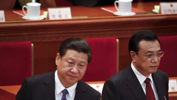 Chinese President Xi Jinping, left, and Chinese Premier Li Keqiang arrive for the closing ceremony of the annual National People's Congress in Beijing's Great Hall of the People, China, Thursday, March 13, 2014. (AP Photo/Vincent Thian)