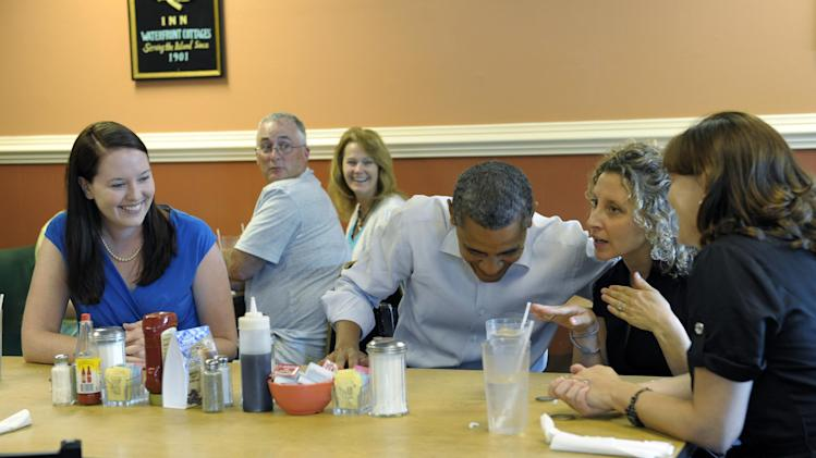 President Barack Obama talks with Jennifer Farlin, second from right, as Amber Herbert, left, and Cari Beauregard, right, listen during a meeting at Rick's Cafe in Virginia Beach, Va., Friday, July 13, 2012. The three women are all military spouses from Chesapeake, Va. Obama is spending the day in Virginia campaigning. (AP Photo/Susan Walsh)