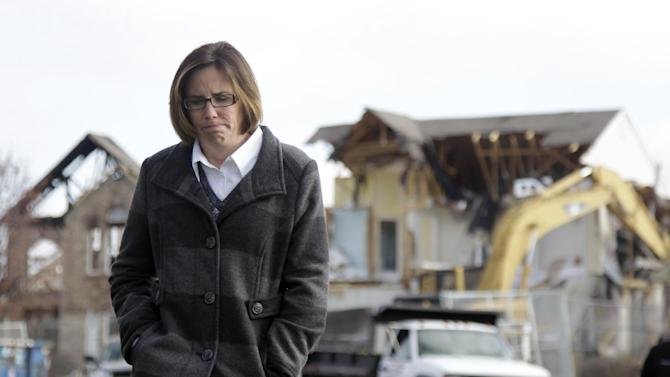 Nikki Cocherell walks away from the site where her home was being demolished in Indianapolis, Tuesday, Nov. 27, 2012.  City building inspectors last week ordered the demolition of 29 houses by Dec. 20. Four other homes, including two that were leveled in the Nov. 10 explosion, are being maintained as police investigate what they believe was an intentional natural gas explosion. (AP Photo/Michael Conroy)