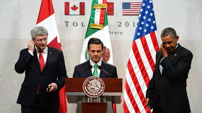 Canada's Prime Minister Stephen Harper, left, and President Barack Obama, right, look on as Mexico's President Enrique Pena Nieto speaks at a news conference during the North American Leaders Summit in Toluca, Mexico, Wednesday, Feb. 19, 2014. Obama is in Toluca for a one-day summit with Mexican and Canadian leaders, meeting on issues of trade and other neighbor-to-neighbor interests, even as Congress is pushing back against some of his top cross-border agenda items. (AP Photo/The Canadian Press, Sean Kilpatrick )
