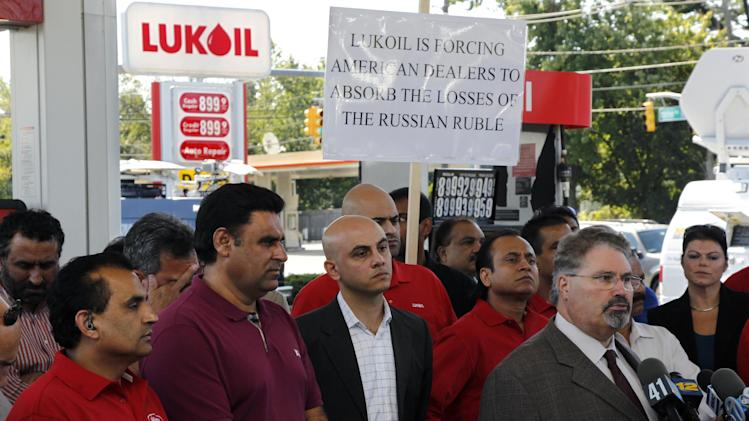 Sal Risalvato, second right, answers a question at a Lukoil service station Wednesday, Sept. 12, 2012, in South Plainfield, N.J., as a large gathering of Lukoil dealers and workers protested what they say are unfair pricing practices by Lukoil North America. More than 50 Lukoil gas stations in New Jersey and Pennsylvania were jacking up prices to more than $8 a gallon Wednesday to protest what they say are unfair pricing practices by Lukoil North America that they say leave them at a competitive disadvantage. Risalvato of the New Jersey Gasoline, Convenience, Automotive Association said the protest was aimed at raising consumer awareness about the challenges facing Lukoil dealers and to get Lukoil to respond to dealer grievances. (AP Photo/Mel Evans)