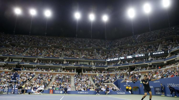Roger Federer of Switzerland returns a shot to Sam Groth of Australia in their men's singles match at the 2014 U.S. Open tennis tournament in New York