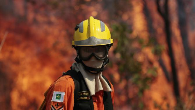 A firefighter looks on during attempts to extinguish flames of forest fire in environmental conservation area near Jaburu Palace, official residence of vice-president, in Brasilia
