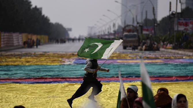 Supporters of Pakistani Sunni Muslim cleric Tahir-ul-Qadri listen to speeches while waiting his arrival to Islamabad, as a youth runs across the street holding a national flag, in Islamabad, Pakistan, Monday, Jan. 14, 2013. Thousands of supporters of the fiery cleric who has been calling for election reforms were descending Monday on the Pakistani capital, where authorities have put up barricades and sent riot police into the streets in preparation. (AP Photo/Muhammed Muheisen)