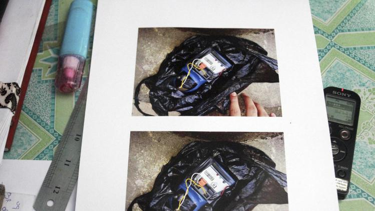 In this photo taken on Monday, Oct. 14, 2013, photographs of a homemade time bomb in a plastic bag found at a restaurant, is displayed at a police station in Yangon, Myanmar. Police urged vigilance after several small bombs exploded in and around Myanmar's largest city of Yangon in recent days. No one claimed responsibility for the blasts and it was not immediately clear if they were related. (AP Photo/Khin Maung Win)