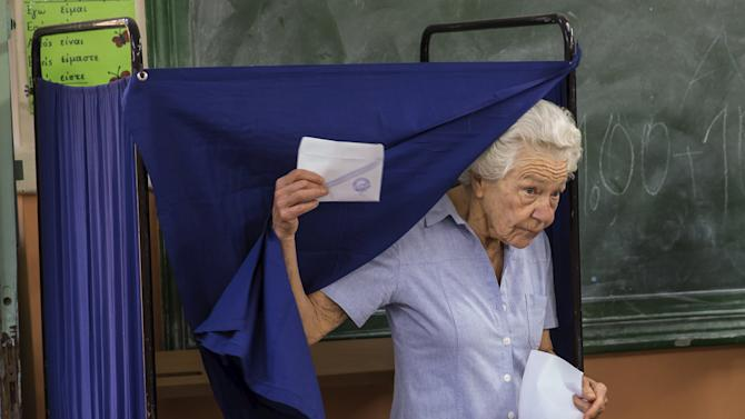 Woman leaves a polling booth to cast her ballot during a referendum vote in Athens