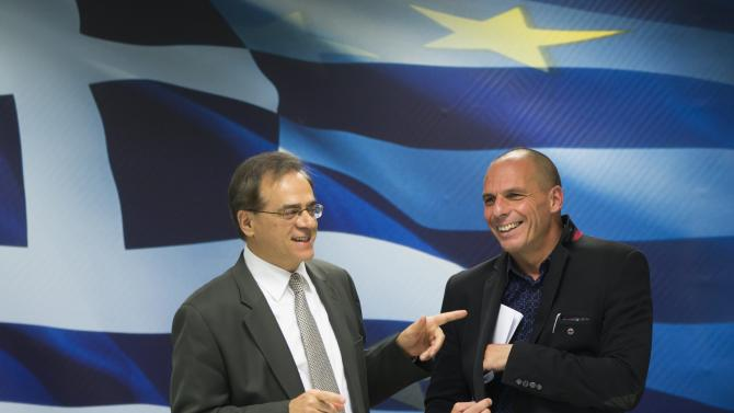 Newly appointed Greek Finance Minister Varoufakis talks to former Finance Minister Hardouvelis during a hand over ceremony in Athens