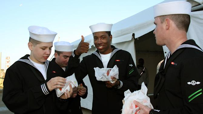 IMAGE DISTRIBUTED FOR TACO BELL - Sailors returning from deployment enjoy free Doritos Locos Tacos handed out by Taco Bell employees during the return of the USS Eisenhower Carrier Strike Group at the Naval Station in Norfolk, Va., on Wednesday, Dec. 19, 2012.  In gratitude for their service, Taco Bell provided the sailors and their families with their first meal after returning from six months of operations in the Middle East. (Lisa Billings/AP Images for Taco Bell)