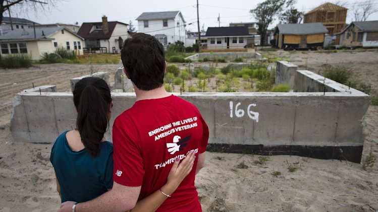 In this Sept. 2, 2013, photo, Joe Quinn and his wife Melanie visit the remains of his parents' home that was destroyed by Superstorm Sandy in the Breezy Point neighborhood of New York's Queens borough. Joe Quinn, whose older brother Jimmy was killed on the 104th floor of the World Trade Center's Tower One on Sept. 11, 2001, lost treasured pictures and hand-written letters from his brother that were among 12 boxes of mementos that were lost in the house when Superstorm Sandy struck the Queens community last October. (AP Photo/John Minchillo)