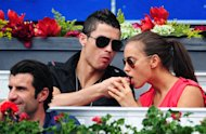MADRID, SPAIN - MAY 12: Real Madrid player Cristiano Ronaldo (C) feeds his girlfriend Irina Shayk a piece of chocolate as Portuguese football legend Luis Figo (L) looks on while attending the semi final match between Roger Federer of Switzerland and Janko Tipsarevic of Serbia during the Mutua Madrilena Madrid Open tennis tournament at the Caja Magica on May 12, 2012 in Madrid, Spain.  (Photo by Jasper Juinen/Getty Images)