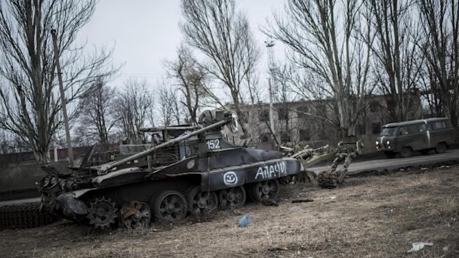 A mini van drives past a damaged Ukrainian military vehicle in Ocheretyno, eastern Ukraine, Monday, March 2, 2015. Complicating the dispute are deliveries to Ukraine's rebel-held east, where fighting between Kiev's forces and Russia-backed rebels has killed nearly 5,800 people. (AP Photo/Evgeniy Maloletka)