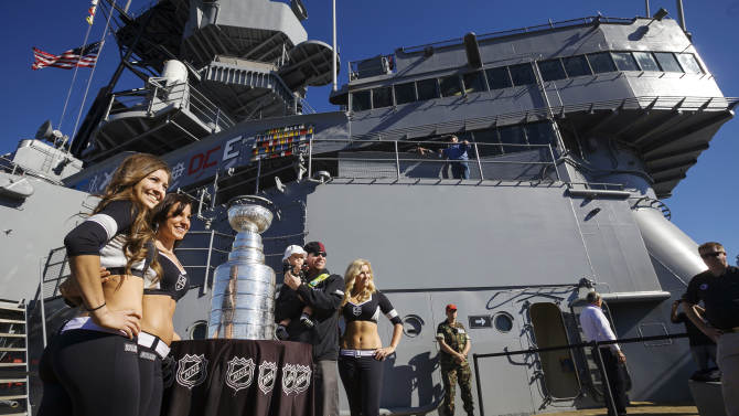 Los Angeles Kings Ice Crew members, from left, Ally, Arsee and Jessica stand with fan Charles Bryant, from Torrance, Calif., and his daughter, Cailey, 1, center, as they pose for photos with the Stanley Cup on tour at the USS Iowa in Los Angeles, Wednesday, Jan. 16, 2013. Hockey's top prize was presented to the Kings, who defeated the New Jersey Devils four games to two in the NHL hockey Stanley Cup finals last June. (AP Photo/Damian Dovarganes)