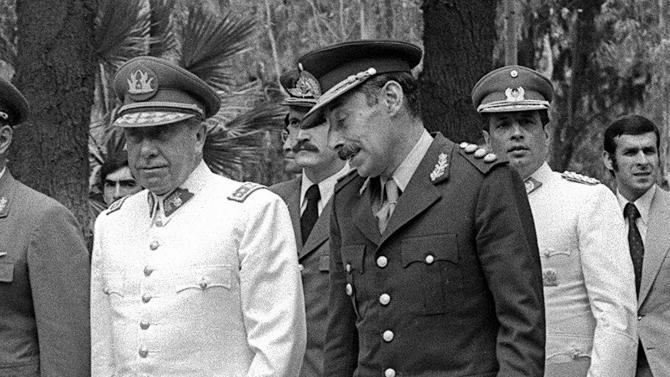 """FILE - In this Jan. 19, 1978 file photo, Argentina's President Gen. Jorge Rafael Videla, right, talks with Chile's Gen. Augusto Pinochet, in Mendoza, Argentina. The former Argentine dictator died of natural causes Friday, May 17, 2013, while serving life sentences at the Marcos Paz prison for crimes against humanity. Videla took power in a 1976 coup and led a military junta that killed thousands of his fellow citizens in a dirty war to eliminate """"subversives."""" He was 87. (AP Photo/Eduardo Di Baia, File)"""