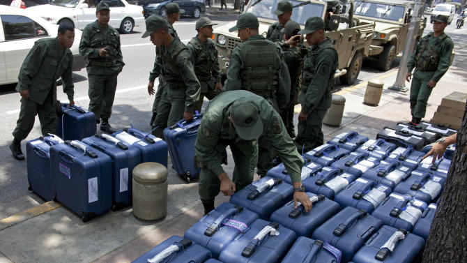 Army soldiers unload cases containing voting machines, outside a polling station in Caracas, Venezuela, Wednesday, April 10, 2013. Venezuela's presidential election is scheduled for Sunday, April 14. (AP Photo/Ramon Espinosa)