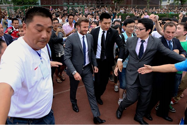 David Beckham walks to meet his fans before a stampede caused by fans storming a security cordon in a university in Shanghai Thursday June 20, 2013. Fans eager to see the soccer superstar stormed a po