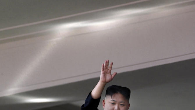 North Korean leader Kim Jong Un waves from a balcony at the end of a mass military parade in Pyongyang's Kim Il Sung Square to celebrate 100 years since the birth of his grandfather, and North Korean founder, Kim Il Sung on Sunday, April 15, 2012. Light at top is reflection of sunlight. (AP Photo/Ng Han Guan)
