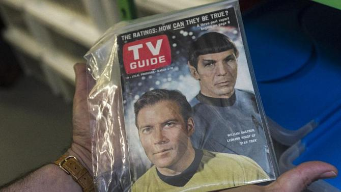 "In this Friday, Nov. 30, 2012 photo, James Comisar holds an original TV Guide issue featuring William Shatner, and Leonard Nimoy of ""Star Trek."" The item is part of his television memorabilia collection in a temperature- and humidity-controlled warehouse in Los Angeles. (AP Photo/Damian Dovarganes)"