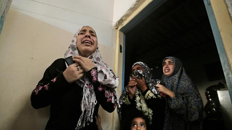 Palestinian mourners cry as the bodies of brothers Abdullah Al Amoudi, 18, and Bilal, 26, who were killed by an Israeli strike earlier near the Abu Hussein school, are brought into their home during their funeral at Jebaliya refugee camp, northern Gaza Strip, Wednesday, July 30, 2014. According to the family, the brothers were killed outside the family home, across the street from the U.N. school. Several Israeli tank shells slammed into the crowded U.N. school used as shelter for refugees in the Gaza war early on Wednesday, killing over a dozen people, a Palestinian health official and a U.N. official said. (AP Photo/Lefteris Pitarakis)