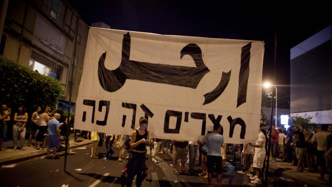 """In this photo taken Saturday, Aug. 6, 2011, Israelis hold up a sign reading """"Leave"""" in Arabic, an Egyptian revolution slogan demanding Egyptian President Hosni Mubarak 's resignation, and """"Egypt, it's here"""" in Hebrew, during a protest against the cost of living in Israel, in central Tel Aviv, Israel. After a quarter million Israelis took to the streets last weekend to protest soaring living prices in Israel, moving the government to promise changes and engagement, some Israelis are starting to wonder whether they have been moved to action, even subconsciously, without foresight or planning, by the Arab Spring. (AP Photo/Dan Balilty)"""