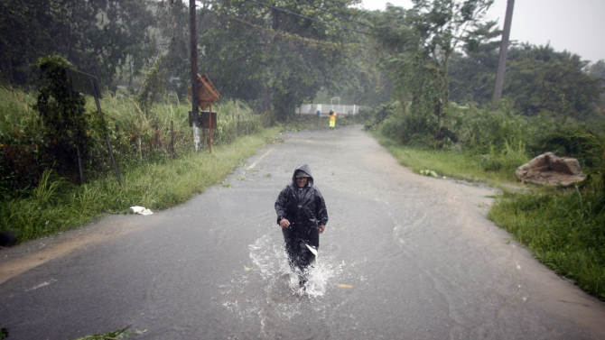 A man wades through a flooded street after hurricane Irene hit the area in Naguabo, Puerto Rico, Monday, Aug. 22, 2011. Hurricane Irene headed out over warm ocean water on a path that could take it to northeastern Dominican Republic and part of Haiti early Tuesday and to the U.S. mainland by the end of the week. (AP Photo/Ricardo Arduengo)