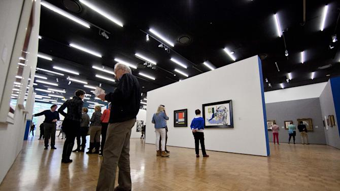 A man admiring a painting holds the catalogue of the Avant-gardes exhibit as the Kunsthal museum reopened its doors to the public following an art heist in Rotterdam, Netherlands, Wednesday, Oct. 17, 2012. Police investigating a multimillion euro (dollar) art heist on early Tuesday morning Oct. 16, 2012, say they are following up several tips from the public, a day after thieves grabbed seven paintings from the walls of a Rotterdam gallery and vanished into the night. A spokeswoman for detectives on the case, Willemieke Romijn, said Wednesday they have some 15 tips from the public, following a late-night, nationally televised appeal for witnesses to the theft from the Kunsthal gallery of works by celebrated artists including Pablo Picasso, Claude Monet and Henri Matisse. (AP Photo/Peter Dejong)