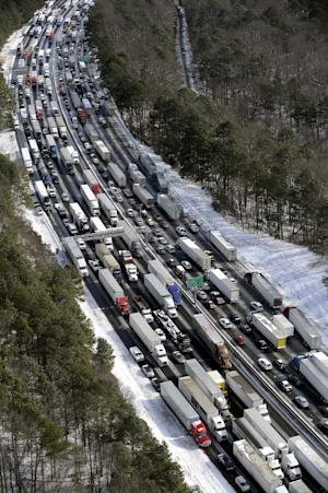 FILE - In this Wednesday, Jan. 29, 2014, file aerial photo, traffic is snarled along the Interstate 285 perimeter, north of the metro area after a winter snowstorm, in Atlanta. With memories of thousands of vehicles gridlocked for hours on icy metro Atlanta highways fresh in their minds, emergency officials and elected leaders in north Georgia were preparing Monday, Feb. 10, 2014, for another round of winter weather. (AP Photo/David Tulis, File)