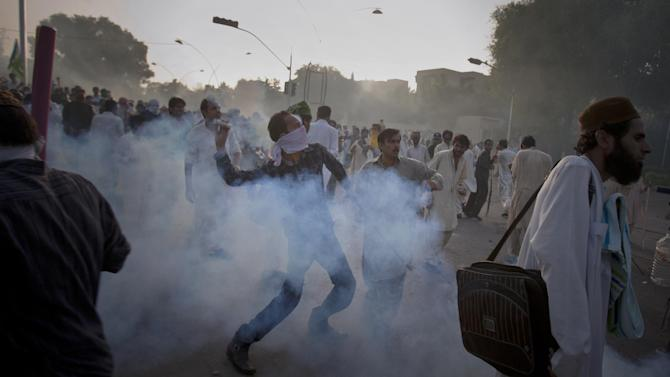 """A Pakistani protestor hurls back a tear gas canister fired by police during clashes that erupted as the demonstrators tried to approach the U.S. embassy in Islamabad, Pakistan, Friday, Sept. 21, 2012. Over a dozen people were killed as tens of thousands protested against the film around the country after the government encouraged peaceful protests and declared a national holiday — """"Love for the Prophet Day."""" Demonstrations turned violent in several Pakistani cities. (AP Photo/Anjum Naveed)"""