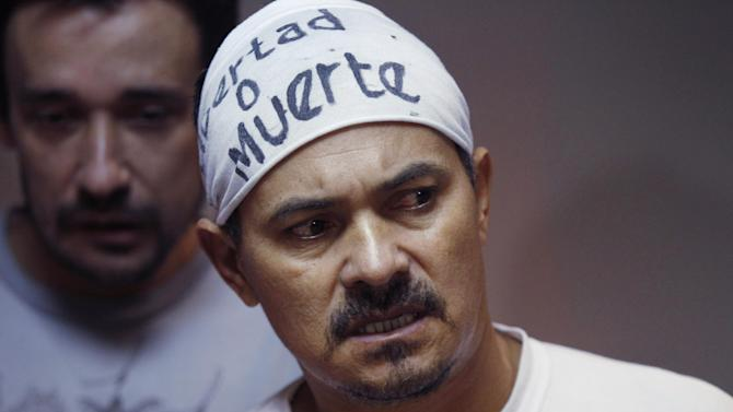 "Imprisoned landless farmer leader Ruben Villalba, who is on his 17th day of a hunger strike, wears a sign on his head that reads in Spanish ""Freedom or death"" as he attends his pre-trial hearing at court in Col. Oviedo city, Paraguay, Thursday, Feb. 14, 2013. Behind is fellow farmer Nestor Castro, who is also on a hunger strike. The prosecutor says he has no physical evidence showing who killed six police officers during a bloody land dispute that prompted the downfall of Paraguayan President Fernando Lugo. He says he didn't even try to determine who killed 11 farm workers who also died when the bullets started flying. Villalba and Castro are on hunger strike to protest their eight month imprisonment without formal charges. (AP Photo/Jorge Saenz)"